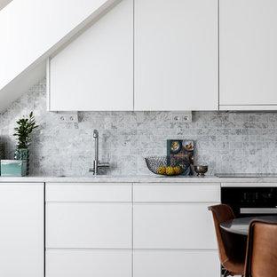 Inredning av ett minimalistiskt kök, med en undermonterad diskho, släta luckor, vita skåp, grått stänkskydd och rostfria vitvaror