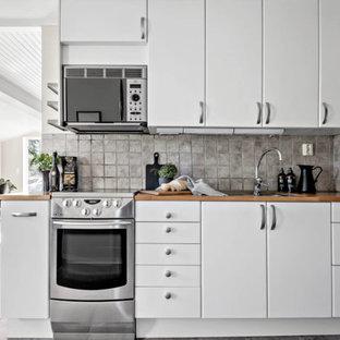 Inspiration för ett litet minimalistiskt beige linjärt beige kök och matrum, med en dubbel diskho, släta luckor, vita skåp, träbänkskiva, flerfärgad stänkskydd, stänkskydd i stenkakel, rostfria vitvaror, skiffergolv och flerfärgat golv