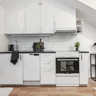 Small modern single-wall open plan kitchen in Stockholm with a double-bowl sink, flat-panel cabinets, white cabinets, laminate benchtops, white splashback, porcelain splashback, white appliances, light hardwood floors, beige floor and black benchtop.