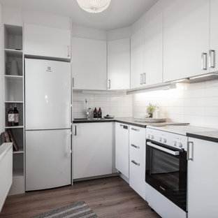 Small scandinavian open concept kitchen ideas - Example of a small danish l-shaped open concept kitchen design in Stockholm with flat-panel cabinets, white cabinets, laminate countertops, white backsplash, porcelain backsplash, white appliances, no island and black countertops