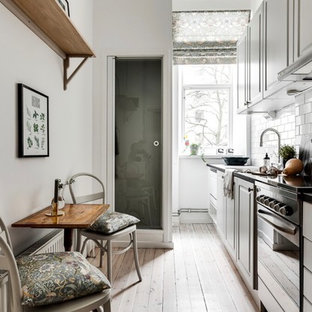Inspiration for a small scandinavian single-wall eat-in kitchen in Stockholm with white cabinets, light hardwood floors, no island, raised-panel cabinets, white splashback, subway tile splashback and beige floor.