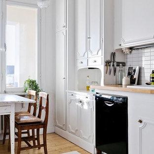 Foto på ett mellanstort vintage linjärt kök och matrum, med luckor med infälld panel, vita skåp, träbänkskiva, vitt stänkskydd, svarta vitvaror och mellanmörkt trägolv