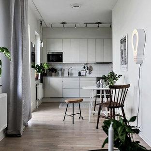 Inredning av ett minimalistiskt linjärt kök och matrum, med släta luckor, grå skåp, vitt stänkskydd, rostfria vitvaror, ljust trägolv och beiget golv