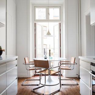 Exempel på ett mellanstort nordiskt kök, med en undermonterad diskho, släta luckor, vita skåp, vitt stänkskydd, stänkskydd i tunnelbanekakel och mellanmörkt trägolv