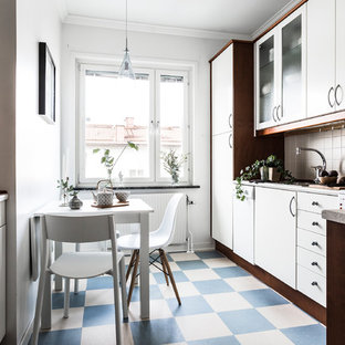 Mid-sized scandinavian l-shaped eat-in kitchen in Stockholm with flat-panel cabinets, white cabinets, beige splashback, no island and blue floor.