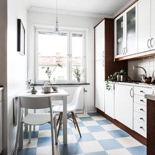 Modelo de cocina comedor en L, escandinava, de tamaño medio, sin isla, con armarios con paneles lisos, puertas de armario blancas, salpicadero beige y suelo azul