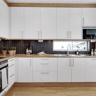 Exempel på ett nordiskt brun brunt l-kök, med en dubbel diskho, släta luckor, vita skåp, träbänkskiva, svart stänkskydd, stänkskydd i mosaik, rostfria vitvaror, ljust trägolv och beiget golv