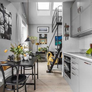 Inspiration för små minimalistiska linjära grått kök med öppen planlösning, med släta luckor, grå skåp, marmorbänkskiva, vitt stänkskydd, stänkskydd i porslinskakel, ljust trägolv och beiget golv