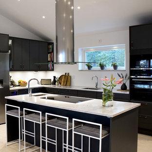 Idéer för ett mellanstort skandinaviskt vit l-kök, med en enkel diskho, släta luckor, svarta skåp, bänkskiva i kvarts, vitt stänkskydd, svarta vitvaror, laminatgolv, en köksö och beiget golv