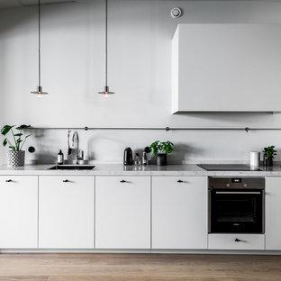 Minimalistisk inredning av ett mellanstort linjärt kök med öppen planlösning, med en enkel diskho, släta luckor, vita skåp, marmorbänkskiva, vitt stänkskydd, rostfria vitvaror, mellanmörkt trägolv och brunt golv