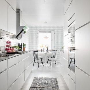 Inredning av ett skandinaviskt kök, med släta luckor, en undermonterad diskho, vita skåp, vitt stänkskydd, vitt golv och målat trägolv