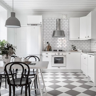 Design ideas for a scandinavian l-shaped eat-in kitchen in Stockholm with flat-panel cabinets, white cabinets, white splashback, subway tile splashback, white appliances and multi-coloured floor.