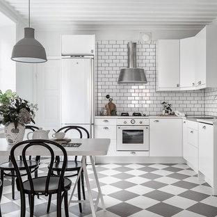 Inredning av ett minimalistiskt kök, med släta luckor, vita skåp, vitt stänkskydd, stänkskydd i tunnelbanekakel, vita vitvaror och flerfärgat golv