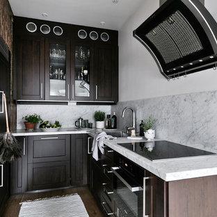 Foto på ett litet minimalistiskt grå kök, med luckor med glaspanel, skåp i mörkt trä, marmorbänkskiva, grått stänkskydd, stänkskydd i marmor, en nedsänkt diskho, svarta vitvaror, mellanmörkt trägolv och brunt golv