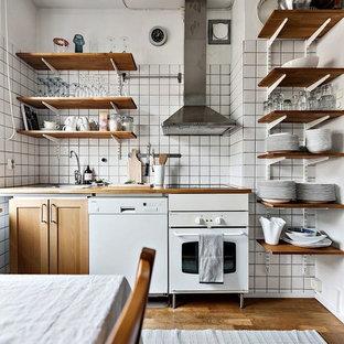 Diseño de cocina lineal, urbana, pequeña, abierta, con puertas de armario de madera oscura, encimera de madera, salpicadero blanco, salpicadero de azulejos de vidrio y suelo de madera en tonos medios