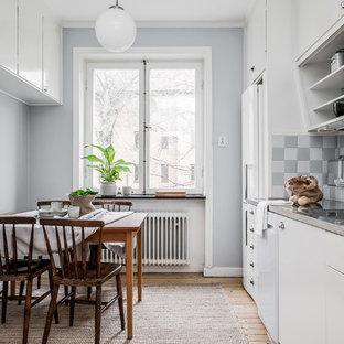 Foto på ett 60 tals grå linjärt kök och matrum, med en integrerad diskho, släta luckor, vita skåp, bänkskiva i rostfritt stål, flerfärgad stänkskydd, vita vitvaror, ljust trägolv och beiget golv