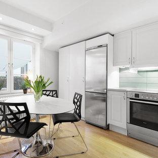 Inspiration för ett mellanstort vintage linjärt kök och matrum, med luckor med upphöjd panel, vita skåp, blått stänkskydd, stänkskydd i glaskakel, rostfria vitvaror och ljust trägolv