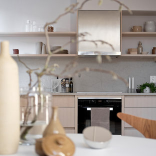 This is an example of a mid-sized scandinavian l-shaped open plan kitchen in Stockholm with an undermount sink, limestone benchtops, limestone splashback, stainless steel appliances, light hardwood floors and no island.