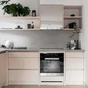 Inspiration för ett litet nordiskt kök, med släta luckor, skåp i ljust trä, bänkskiva i betong, ljust trägolv, en halv köksö, beiget golv, en undermonterad diskho, grått stänkskydd och svarta vitvaror