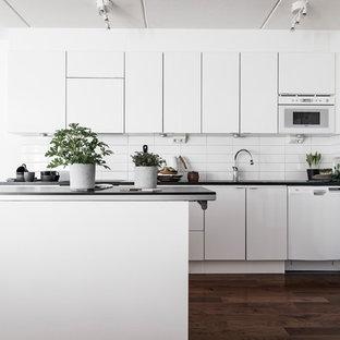 Inredning av ett skandinaviskt mellanstort kök, med släta luckor, vita skåp, vita vitvaror, en köksö, vitt stänkskydd och mörkt trägolv