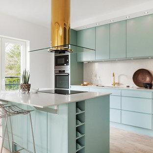 Exempel på ett modernt kök, med en undermonterad diskho, släta luckor, turkosa skåp, vitt stänkskydd, rostfria vitvaror, ljust trägolv, en köksö och beiget golv
