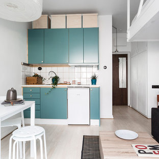 Photo of a small scandinavian single-wall open plan kitchen in Stockholm with flat-panel cabinets, turquoise cabinets, white splashback, white appliances, light hardwood floors, no island and beige floor.