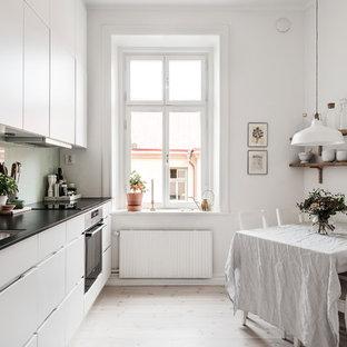 Inredning av ett skandinaviskt linjärt kök, med en undermonterad diskho, släta luckor, vita skåp, grönt stänkskydd, rostfria vitvaror, ljust trägolv och beiget golv