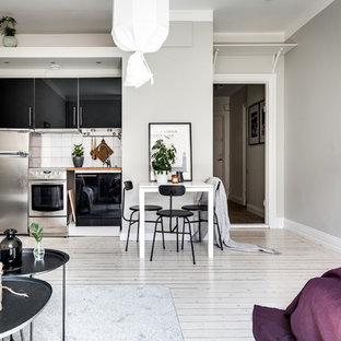 Idéer för att renovera ett litet minimalistiskt linjärt kök med öppen planlösning, med släta luckor, svarta skåp, träbänkskiva, vitt stänkskydd, ljust trägolv och vitt golv