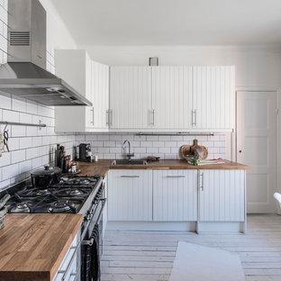 Foto på ett lantligt kök, med en nedsänkt diskho, vita skåp, träbänkskiva, vitt stänkskydd, stänkskydd i tunnelbanekakel, rostfria vitvaror, ljust trägolv och vitt golv