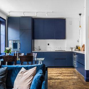 Exempel på ett nordiskt kök, med släta luckor, blå skåp, grått stänkskydd, rostfria vitvaror, mellanmörkt trägolv och brunt golv