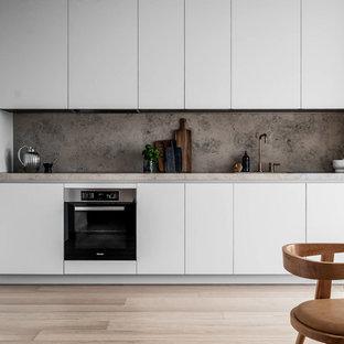 Idéer för att renovera ett funkis grå grått kök, med släta luckor, vita skåp, grått stänkskydd, stänkskydd i sten, ljust trägolv och beiget golv