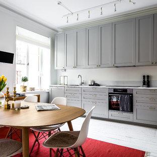 Exempel på ett nordiskt kök, med skåp i shakerstil, grå skåp, grått stänkskydd, svarta vitvaror, målat trägolv och vitt golv