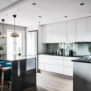 Idéer för mellanstora funkis linjära kök, med släta luckor, vita skåp, granitbänkskiva, ljust trägolv, blått stänkskydd, glaspanel som stänkskydd och beiget golv