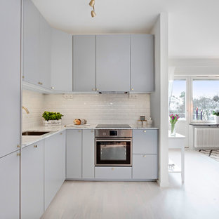 Small contemporary eat-in kitchen designs - Inspiration for a small contemporary l-shaped light wood floor eat-in kitchen remodel in Stockholm with a drop-in sink, gray cabinets, marble countertops, white backsplash, cement tile backsplash and stainless steel appliances