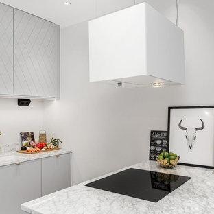 Idéer för att renovera ett litet skandinaviskt kök, med en undermonterad diskho, släta luckor, grå skåp, en halv köksö, marmorbänkskiva, grått stänkskydd, stänkskydd i stenkakel, rostfria vitvaror och ljust trägolv