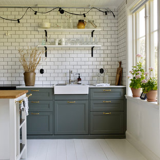 This is an example of a mid-sized scandinavian single-wall kitchen in Stockholm with a single-bowl sink, shaker cabinets, green cabinets, white splashback, painted wood floors and with island.