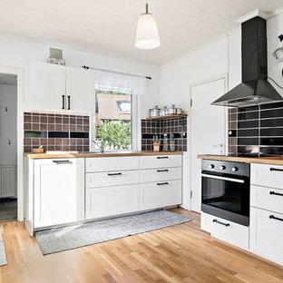 Foto på ett mellanstort nordiskt kök, med vita skåp, träbänkskiva, mellanmörkt trägolv, en dubbel diskho, svart stänkskydd, stänkskydd i keramik och skåp i shakerstil