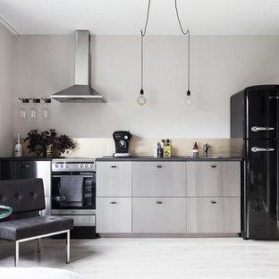 Idéer för ett litet skandinaviskt linjärt kök med öppen planlösning, med släta luckor, skåp i rostfritt stål, stänkskydd med metallisk yta och ljust trägolv
