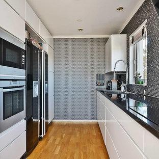 Exempel på ett mellanstort modernt linjärt kök, med en undermonterad diskho, släta luckor, vita skåp, stänkskydd med metallisk yta, rostfria vitvaror och ljust trägolv