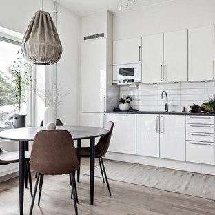 Foto på ett mellanstort skandinaviskt linjärt kök och matrum, med släta luckor, vita skåp, vitt stänkskydd, ljust trägolv och beiget golv