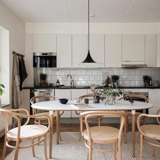 Idéer för ett skandinaviskt svart kök, med en dubbel diskho, släta luckor, vita skåp, vitt stänkskydd, rostfria vitvaror och mellanmörkt trägolv