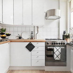 Small scandinavian kitchen pictures - Small danish l-shaped medium tone wood floor kitchen photo in Stockholm with flat-panel cabinets, white cabinets, wood countertops, white backsplash, stainless steel appliances and no island