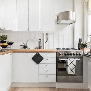 Idée de décoration pour une petite cuisine nordique en L avec un placard à porte plane, des portes de placard blanches, un plan de travail en bois, une crédence blanche, un électroménager en acier inoxydable, aucun îlot et un sol en bois brun.
