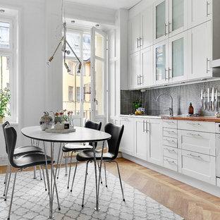 Skandinavisk inredning av ett stort linjärt kök och matrum, med vita skåp, träbänkskiva, stänkskydd i mosaik, vita vitvaror, svart stänkskydd, ljust trägolv och skåp i shakerstil