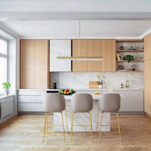 Idéer för ett stort modernt grå kök, med en undermonterad diskho, släta luckor, beige skåp, grått stänkskydd, stänkskydd i porslinskakel, integrerade vitvaror, mellanmörkt trägolv, en köksö och beiget golv