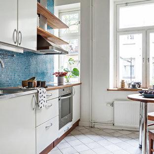 Foto på ett mellanstort funkis linjärt kök och matrum, med en integrerad diskho, släta luckor, beige skåp, bänkskiva i rostfritt stål, blått stänkskydd, stänkskydd i mosaik, rostfria vitvaror och grått golv