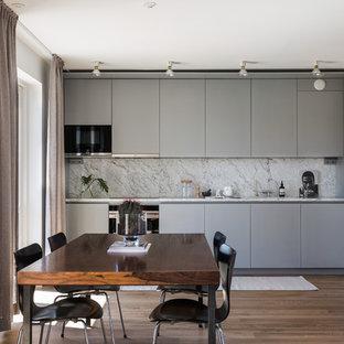 Modern inredning av ett mellanstort linjärt kök, med släta luckor, grå skåp, marmorbänkskiva, grått stänkskydd och mellanmörkt trägolv