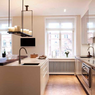 Mid-sized contemporary eat-in kitchen ideas - Eat-in kitchen - mid-sized contemporary dark wood floor and brown floor eat-in kitchen idea in Stockholm with a single-bowl sink, flat-panel cabinets, gray cabinets, concrete countertops, white backsplash, glass sheet backsplash, stainless steel appliances and an island