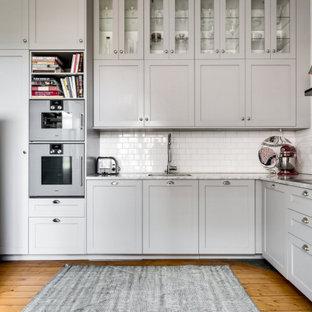 ストックホルムの中サイズのヴィクトリアン調のおしゃれなキッチン (ドロップインシンク、インセット扉のキャビネット、グレーのキャビネット、大理石カウンター、白いキッチンパネル、セラミックタイルのキッチンパネル、シルバーの調理設備の、無垢フローリング、アイランドなし、ベージュの床、白いキッチンカウンター) の写真
