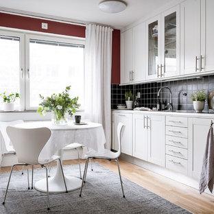 Inredning av ett minimalistiskt mellanstort linjärt kök och matrum, med luckor med infälld panel, vita skåp, bänkskiva i rostfritt stål, svart stänkskydd, ljust trägolv och beiget golv